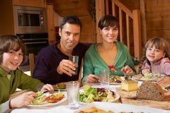 Familia que disfruta de la comida en chalet alpestre junto imagen de archivo