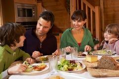 Familia que disfruta de la comida en chalet alpestre junto Imagen de archivo libre de regalías