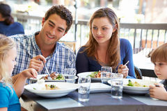 Familia que disfruta de la comida en el restaurante al aire libre Fotos de archivo