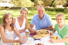 Familia que disfruta de la comida en jardín Fotos de archivo