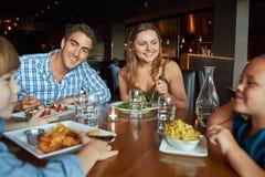 Familia que disfruta de la comida en restaurante Foto de archivo libre de regalías