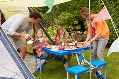 Familia que disfruta de la comida fuera de la tienda en acampada Imágenes de archivo libres de regalías