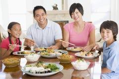 Familia que disfruta de la comida, mealtime junto Foto de archivo libre de regalías