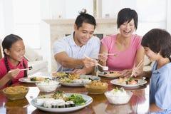 Familia que disfruta de la comida, mealtime junto Fotografía de archivo libre de regalías