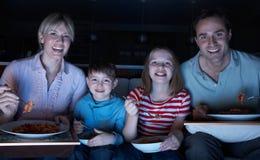 Familia que disfruta de la comida mientras que ve la TV Imagen de archivo