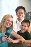 Familia que disfruta de la comunicación de la célula texting Foto de archivo