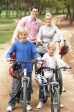Familia que disfruta de paseo de la bici en parque Fotos de archivo libres de regalías