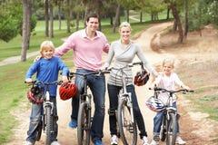 Familia que disfruta de paseo de la bici en parque Imagen de archivo libre de regalías