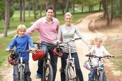 Familia que disfruta de paseo de la bici en parque Fotos de archivo