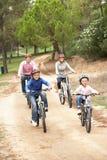 Familia que disfruta de paseo de la bici en parque Imágenes de archivo libres de regalías