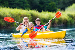Familia que disfruta de paseo del kajak en un río Imagenes de archivo