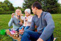 Familia que disfruta de su tiempo con las burbujas de jabón Día libre con el jabón Fotografía de archivo