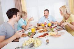 Familia que disfruta de una comida junto Foto de archivo libre de regalías