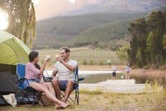Familia que disfruta de vacaciones que acampan por el lago junto fotos de archivo libres de regalías