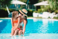 Familia que disfruta de vacaciones de verano en piscina de lujo imagenes de archivo