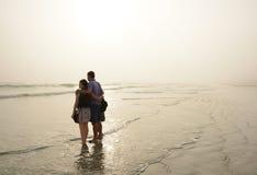 Familia que disfruta del tiempo junto en la playa de niebla hermosa Imagenes de archivo