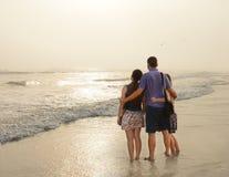 Familia que disfruta del tiempo junto en la playa de niebla hermosa Imágenes de archivo libres de regalías