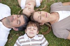 Familia que duerme al aire libre con las pistas junto Imagen de archivo