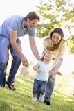 Familia que ejecuta al aire libre la sonrisa Fotografía de archivo