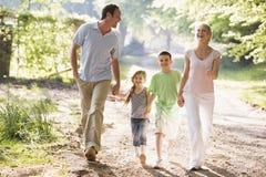 Familia que ejecuta al aire libre llevar a cabo las manos y la sonrisa Imágenes de archivo libres de regalías