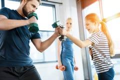 Familia que ejercita con pesas de gimnasia en el estudio de la aptitud Fotos de archivo