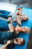 Familia que ejercita con pesas de gimnasia en el estudio de la aptitud Imagenes de archivo