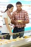 Familia que elige la comida en las compras en supermercado Imagen de archivo
