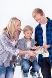 Familia que elige un color para la pared de pintura Imágenes de archivo libres de regalías