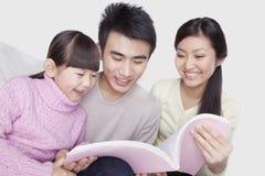 Familia que enlaza junto, sonriendo y leyendo en el sofá, mirando abajo el libro, tiro del estudio Imagen de archivo libre de regalías