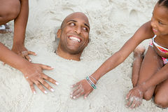 Familia que entierra al padre en arena Imagen de archivo