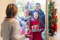 Familia que entrega presentes en la Navidad Imagenes de archivo