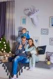 Familia que espera un Año Nuevo Familia con el pequeño hijo que sienta el ne Imagen de archivo