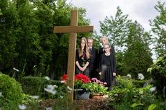 Familia que está de luto en el sepulcro en cementerio imagen de archivo libre de regalías