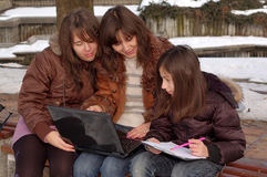 Familia que estudia la computadora portátil imagen de archivo