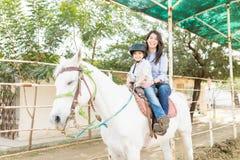 Familia que experimenta programa equino de la terapia imagen de archivo