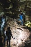Familia que explora la cueva enorme Los viajeros de la aventura vistieron el sombrero de vaquero y la mochila, grupo de personas  fotos de archivo