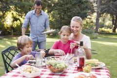 Familia que goza de la barbacoa en jardín junto Imágenes de archivo libres de regalías
