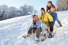 Familia que goza de la colina de Sledging abajo Nevado Imágenes de archivo libres de regalías