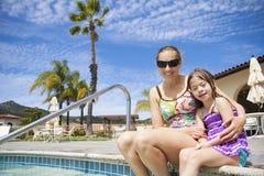 Familia que goza de la piscina Foto de archivo