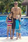 Familia que goza de la piscina en un centro turístico tropical Foto de archivo