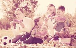 Familia que goza de la sandía en comida campestre Foto de archivo