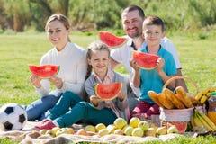 Familia que goza de la sandía en comida campestre Foto de archivo libre de regalías