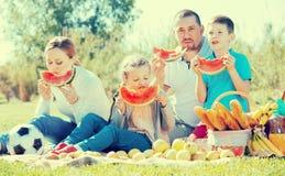Familia que goza de la sandía en comida campestre Imagenes de archivo