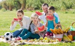 Familia que goza de la sandía en comida campestre Fotografía de archivo libre de regalías