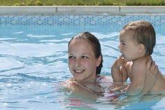 Familia que goza de una piscina Foto de archivo libre de regalías