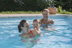 Familia que goza de una piscina Imágenes de archivo libres de regalías