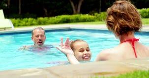 Familia que goza en piscina almacen de metraje de vídeo