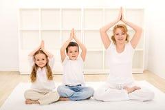 Familia que hace ejercicios de la yoga Fotos de archivo libres de regalías