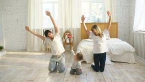 Familia que hace ejercicios gimnásticos en la educación sana de la vida del dormitorio en casa - metrajes