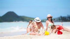 Familia que hace el castillo de la arena en la playa blanca el vacaciones de verano almacen de video
